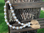 Wooden Bead Garland (White and Natural) Tan Yarn Tassels is shown displayed outside on a ladder.