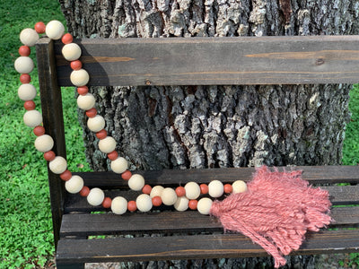 Wooden Bead Garland (Rustic Orange and Natural) Rustic Orange Yarn Tassels is shown displayed outside on a ladder.