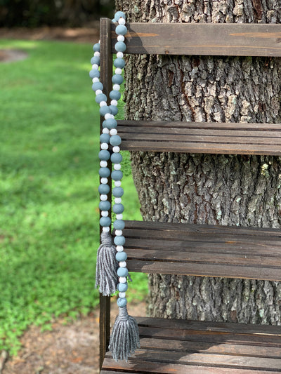 "Wooden Bead Garland (Gray and White) Gray Yarn Tassels is shown in the 45"" garland outside on a ladder."