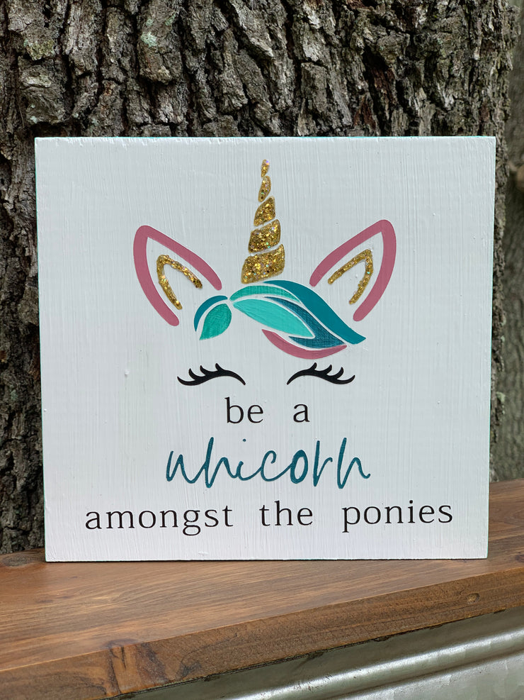 Be A Unicorn Amongst The Ponies shows a closeup of the hand painted sign.  The horn and ears have gold glitter and the word unicorn is highlighted in a turquoise color to stand out.