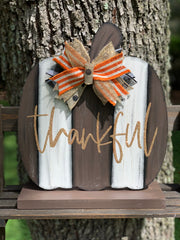 Wood Pallet Pumpkin With Stand is shown sitting outside on a ladder.  This distressed painted pumpkin pallet sign has the work thankful hand painted in gold glitter with our signature burlap bow that is removable.