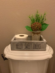 Bathroom Box Organizer - Image is shown on the back of the toilet. Writing says Hello Sweet Cheeks. Can be placed on the back of your toilet or on a shelf or counter top.  Image does not include toilet paper or glass jar with floral arrangement.