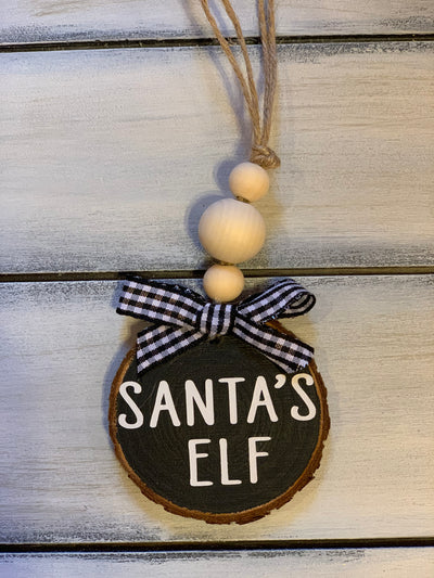 Santa's Elf Christmas Ornament is shown with black background and white font writing and a buffalo plaid ribbon.