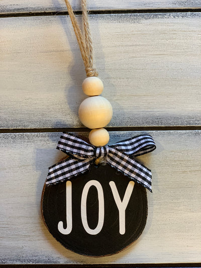 Joy Wooden Beaded Ornament shows an image of the black ornament with a buffalo plaid ribbon. Ribbon selections will vary due to demand.