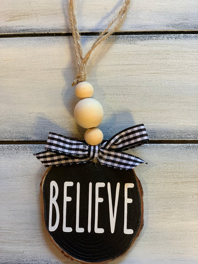Believe Wooden Christmas Ornament is shown with a buffalo plaid ribbon and 3 wooden beads.  Ribbon selection may vary due to demand.