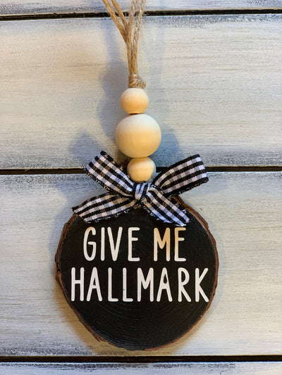 Give Me Hallmark Christmas Ornament is shown with a buffalo plaid ribbon and 3 wooden beads.  Ribbon selection will vary due to demand.