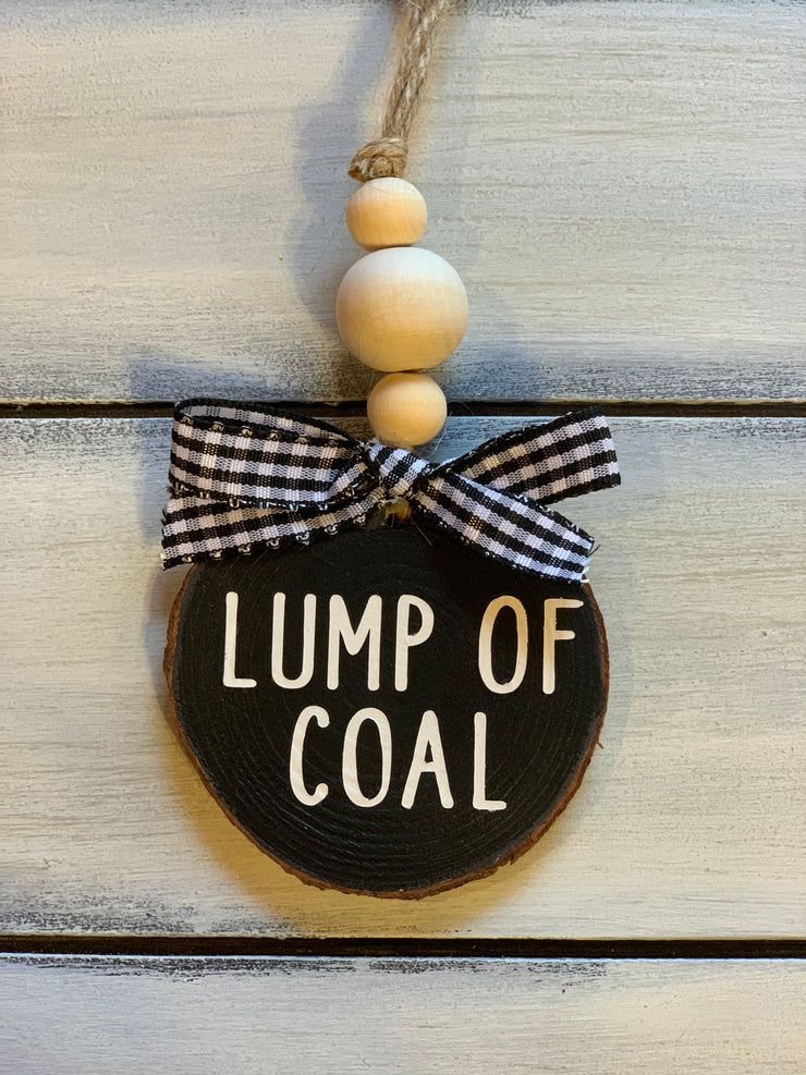 Lump Of Coal Christmas Ornament is shown with a buffalo plain ribbon.  Ribbon will vary due to demand.
