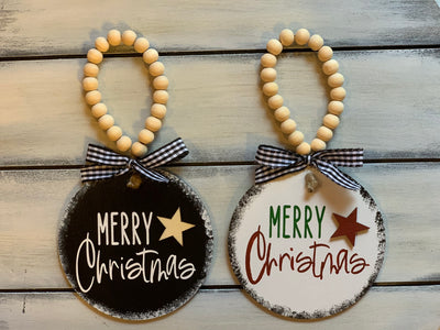 Merry Christmas 4x4 Wood Ornament is shown with a white and black ornament.  The writing on the black ornament is white with a natural wood star and wood beads.  The white ornament has green writing for Merry and red writing for Christmas with a red wooden star and beads.  Both have a buffalo plaid ribbon.  Ribbon may vary due to demand.
