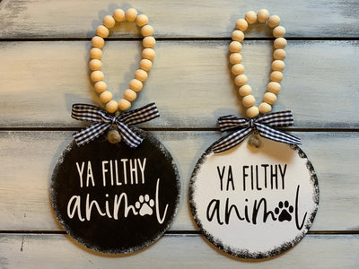 Ya Filthy Animal 4x4 Wood Ornament shows both the black and white ornament with buffalo plaid ribbon and beaded hanger.  Ribbon selection may vary due to demand.  Each ornament is sold separately.