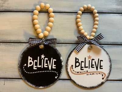 Believe 4x4 Wood Ornament shows both the black and white ornaments with buffalo plaid ribbon and wooden bead to hang.  Ribbons may vary due to demand.  Each ornament sold separately.