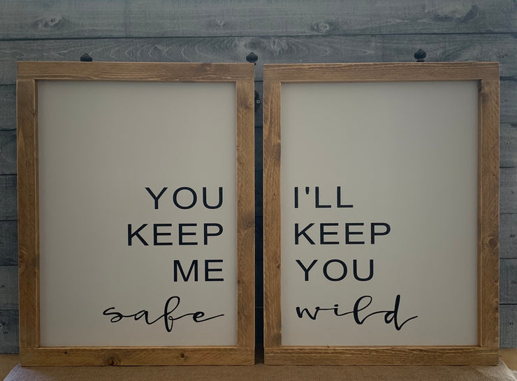 You Keep Me Safe I'll Keep You Wild shows an image of two signs side by side.  White base with black lettering and a distressed natural base stained frame.