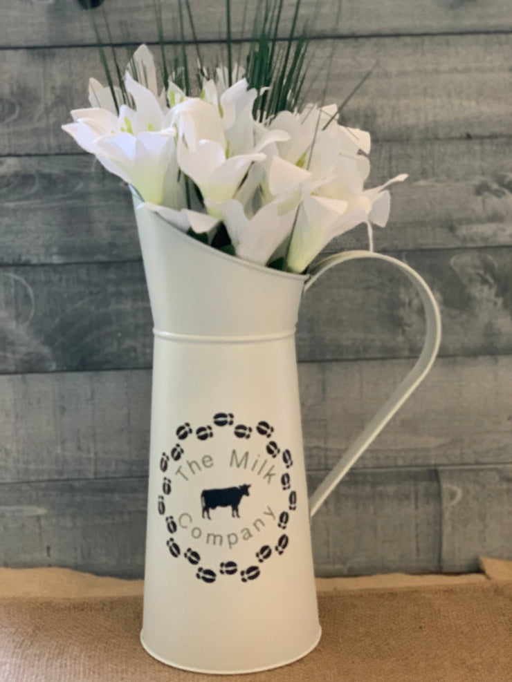 Vintage White Metal Milk Pitcher shows image sitting on a table with a floral arrangement.  Flowers not sold with pitcher.