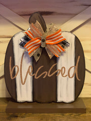This image shows the blessed wood pumpkin cutout mounted on the stand.