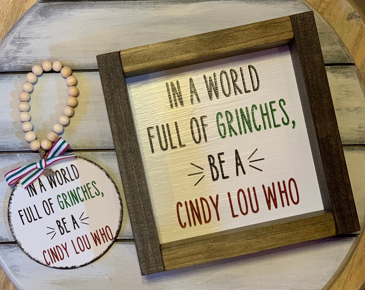 In A World Full of Grinches, Be A Cindy Lou Who 7x7 Sign is shown with the matching ornament.  Each product sold separately.