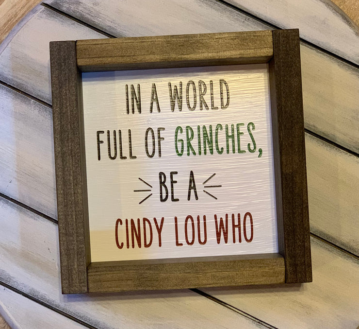In A World Full of Grinches, Be A Cindy Lou Who 7x7 Sign shows the sign by itself with the word Grinch in green paint and Cindy Lou Who in red paint.