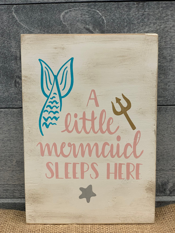 A Little Mermaid Sleeps Here shows an image of the block sign sitting on a table.