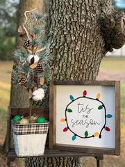 Tis The Season holiday light sign is shown sitting outside on a ladder with our galvanized metal Christmas tree.  Each item is sold separately.