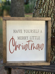 "Have Yourself A Merry Little Christmas is shown sitting outside on a ladder.  This jacobean stained shadowbox frame highlights the white background with black hand painted ""have yourself a merry little"" and hand painted red ""Christmas""."