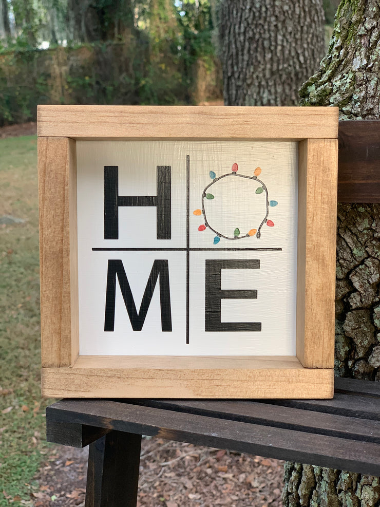 "Home Small Sign with Christmas Lights has the Christmas light strand for the""O"".  With a light natural stained frame, this sign will make the perfect addition to any decor."