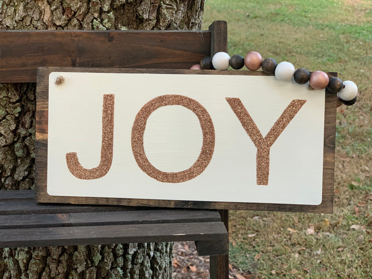 Joy Rose Gold Glitter Sign has hand painted rose gold glitter with hand painted and stained beaded garland.