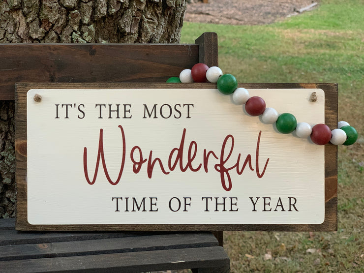 It's The Most Wonderful Time Of The Year sign is shown sitting outside on a ladder.  This beautiful hand painted sign has red, white and green beaded garland to hang.  Add some colorful Christmas cheer to your decor this year.