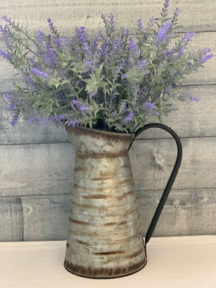 Vintage Galvanized Metal Pitcher shows an image of the pitcher with a floral arrangement sitting on a table.  Flowers are not sold with this item.