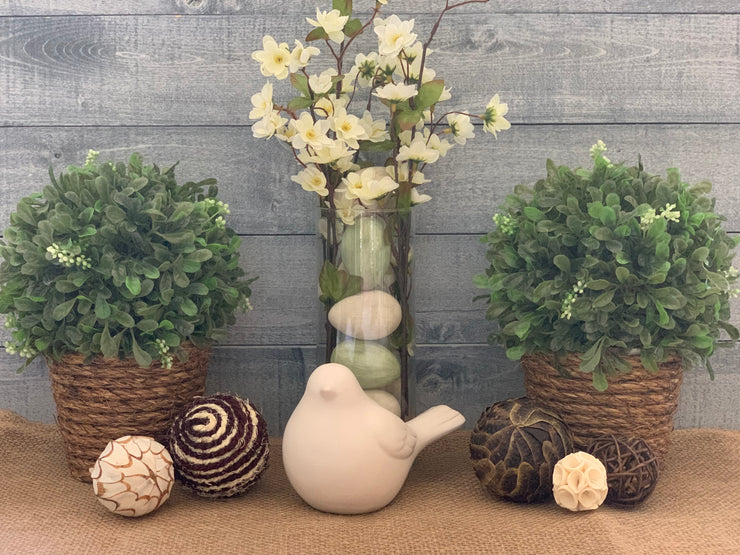 Topiary with Twine Rope shows an image of the topiary sitting on a table as an arrangement with a second topiary, a floral arrangement, a porcelain bird, and decorative balls.