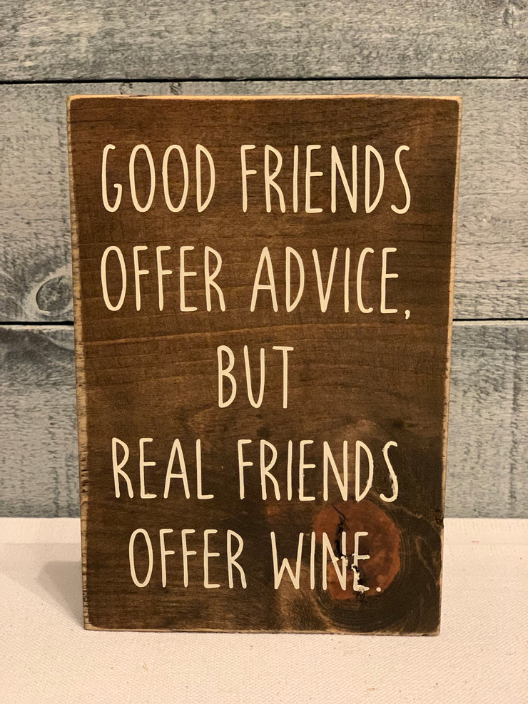 Good Friends Offer Advice, But Real Friends Offer Wine shows an image of a wood block sign sitting on a table.