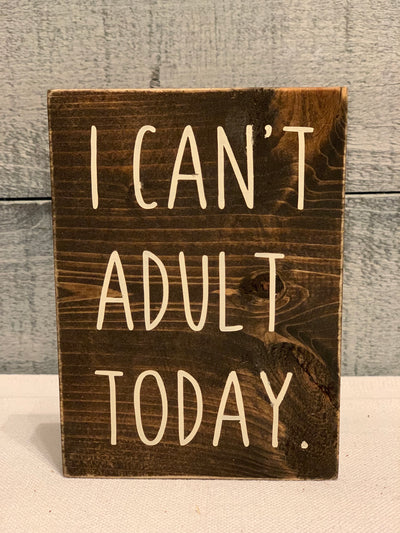 I Can't Adult Today displays an image of a wood block sign on a table.