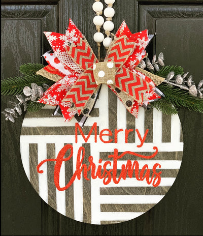 Merry Christmas Door or Wall Hanger is shown hanging on a front door with our signature bow and pine branches with silver embellishments.