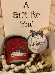 "Home For The Holidays Gift Set includes (1) glass cinnamon scented candle, (1) State/City wooden hand painted 4x4 ornament, (1) 35"" wooden beaded garland and (1) set of matches in a glass container."