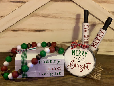 "Merry & Bright Wooden Books / Gift Set shows the gift set items that include Merry & Bright Book Set, 25"" red, green, white and stain garland with twine tassels, the Merry and Bright Wood Painted Ornament with beaded hanger, and two 7"" mini rolling pins that say Merry and Christmas."