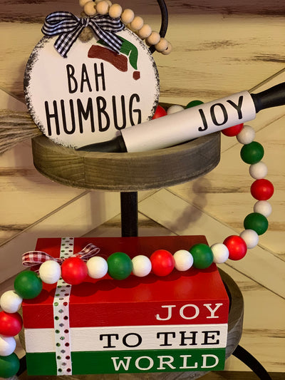 "Joy To The World Wooden Books / Gift Set shows what you will receive in the gift set box.  (1) wood painted Bah Humbug 4x4 Ornament, (1) 7"" mini black and white rolling pin that says JOY, (1) 25"" red, white, and green wood beaded garland, and (1) red, white and green Joy To The World wood book stack."