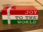 This image shows the Joy To The World red, white and green book stack with a holiday ribbon and bow.