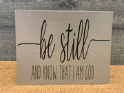 Be Still and Know That I am God shows an image of if the light gray sign sitting on a table.