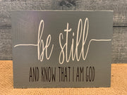 Be Still and Know That I am God shows an image of the dark gray sign sitting on a table.