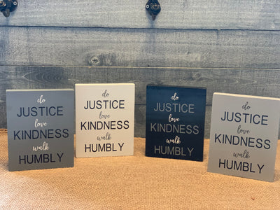 Do Justice, Love Kindness, Walk Humbly shows an image of four block signs dark gray, white, black and light gray sitting on a table.  Each sign sold separately.