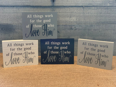 All Things Work For The Good Of Those Who Love Him shows an image of four block signs (white, light gray dark gray, black) sitting on the table.  Each sign is sold separately.