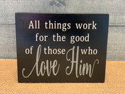 All Things Work For The Good Of Those Who Love Him shows an image of the black sign sitting on a table.