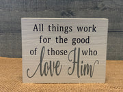 All Things Work For The Good Of Those Who Love Him shows an image of of the white sign sitting on a table.