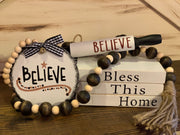 "Bless This Home Wooden Books Gift Set shows the white book set that reads Bless This Home with buffalo plaid ribbon and twine wrap, (1) Jacobean stained and natural beaded garland with twine tassels, (1) hand painted 4x4 wood believe ornament, and (1) 7"" mini rolling pin that says believe in red hand painted lettering."