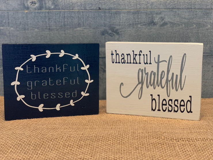 Thankful, Grateful, Blessed (Small Block Sign) show an image of the black and white sign sitting on a table.  Each sign sold separately.
