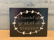 Thankful, Grateful, Blessed (Small Block Sign) shows an image of the black sign sitting on a table.