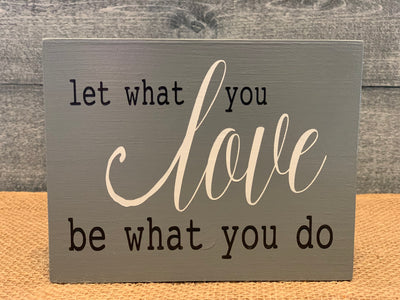Let What You Love Be What You Do shows an image of the dark gray sign sitting on a table.