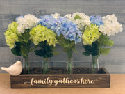 Wood Box Centerpiece shows an image of the family gathers here filled with 4 milk jugs and a floral arrangement.  Floral arrangement, milk jugs and the porcelain bird not sold with box.
