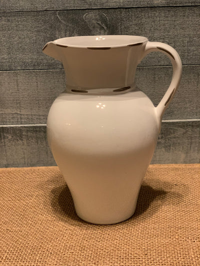 Vintage White Porcelain Pitcher shows an image of the pitcher displayed on a table alone.