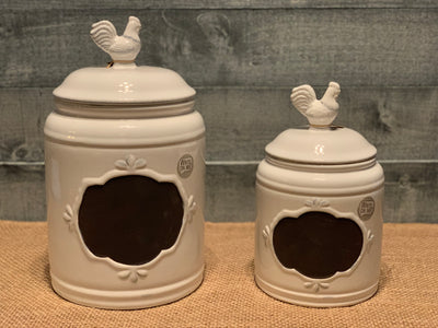 This image shows the large and small white porcelain canisters side by side on a table. Each sold separately.