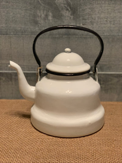 Image shows the white metal tea pot displayed on a table.