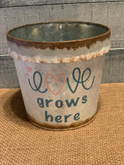 Vintage Galvanized Flower Pot displays an image of an empty flower pot with the words Love Grows Here.