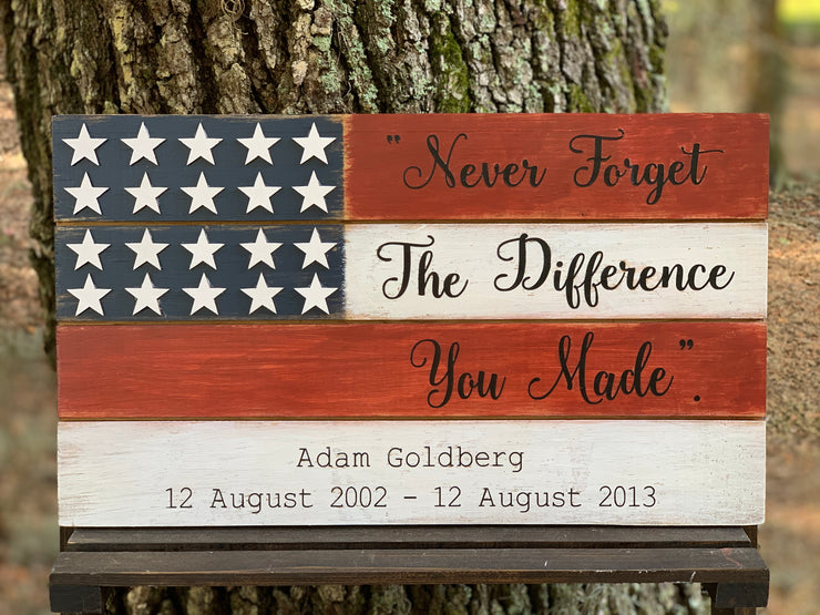 "American Flag Memorial Sign shows the hand painted rustic sign with red and white stripes with black hand painted lettering that reads ""Never Forget The Difference You Made"".  Each name and date of service will be listed below the inscription.  There are 20 one inch wood stars attached to make this look like a 3D sign.  Can be hung on a wall or sit on a shelf."